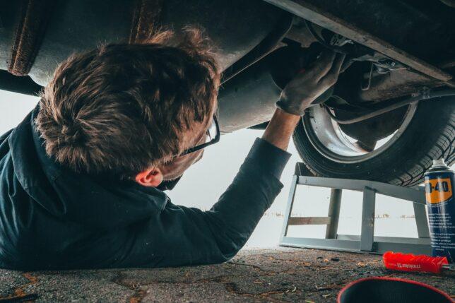 mechanic underneath car fixing things